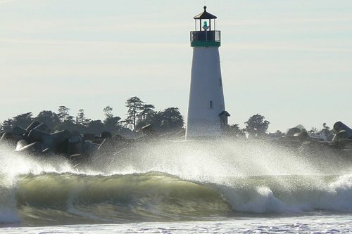 Lighthouse standing strong against pounding waves